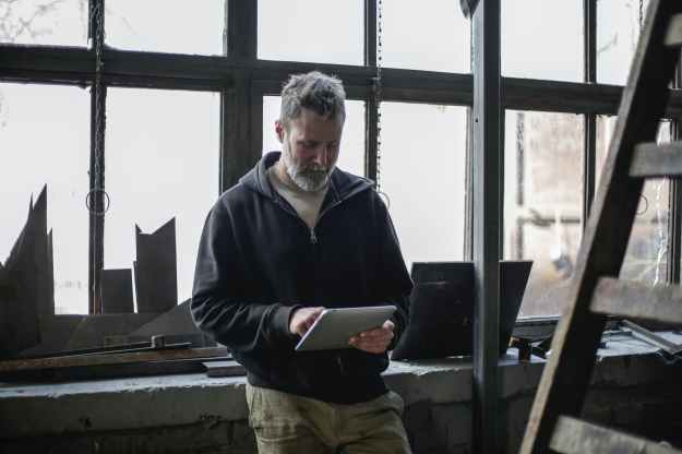 serious adult bearded worker using tablet near window in workshop